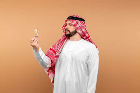 Arab male businessman in national clothes holds an incandescent lamp in his hands. Middle east business concept, good idea, investment 免版税图像