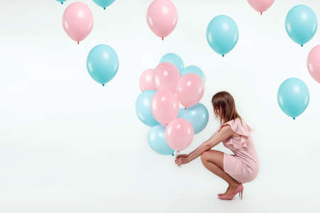 A beautiful young girl sits with blue and pink balloons on a white background. Happiness, spring, holiday