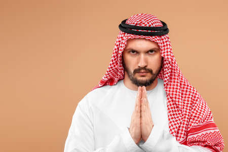 An Arab man in national dress is praying on a beige background. Dishdasha, kandora, thobe ,, traditional men's clothing of the Middle East, islam, faith. Copy space