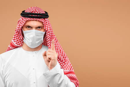 An Arab man in national clothes wearing a medical mask.