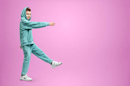 Portrait, cute stylish boy in a blue suit on a pink background. Studio portrait of a child, modern design, trendy background, turquoise. Copy space