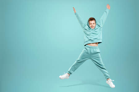 Portrait, cute stylish boy in a blue suit on a blue background. Studio portrait of a child, modern design, trendy background, turquoise. Copy space 版權商用圖片