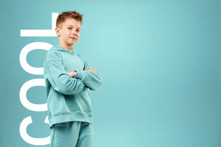 Portrait, cute stylish boy in a blue suit on a blue background. Studio portrait of a child, modern design, trendy background, turquoise. The lettering is cool Stock fotó