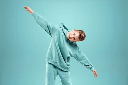 Portrait, cute stylish boy in a blue suit on a blue background. Studio portrait of a child, modern design, trendy background, turquoise. Copy space Stock fotó
