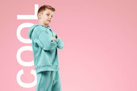 Portrait, cute stylish boy in a blue suit on a pink background. Studio portrait of a child, modern design, trendy background, turquoise. the inscription is cool