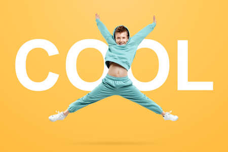 Portrait, cute stylish boy in a blue suit on a yellow background. Studio portrait of a child, modern design, trendy background, turquoise. The lettering is cool Stock fotó
