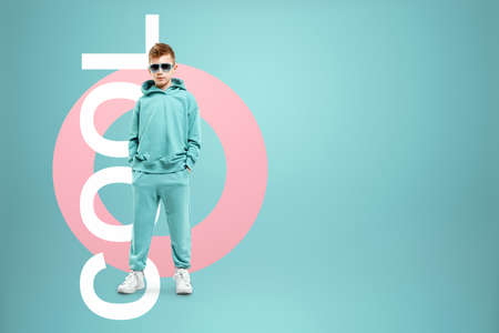 Portrait, cute stylish boy in a blue suit on a blue background. Studio portrait of a child, modern design, trendy background, turquoise. The lettering is cool 版權商用圖片