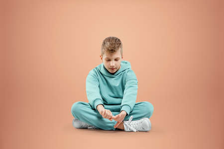 Portrait, cute stylish boy in a blue suit on a beige background. Studio portrait of a child, modern design, trendy background, turquoise. Copy space