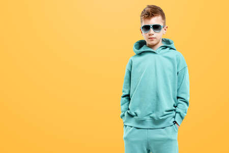 Cute stylish boy in a blue suit on a yellow background. Studio portrait of a child, modern design, trendy background