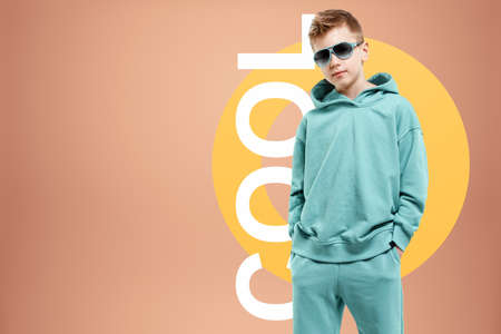 Portrait, cute stylish boy in a blue suit on a beige background. Studio portrait of a child, modern design, trendy background, turquoise. the inscription is cool