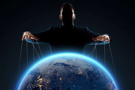 A man, a puppeteer, manipulates the planet. The concept of world conspiracy, world government, manipulation, world control Standard-Bild
