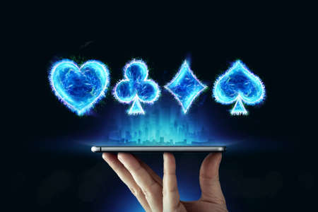 Creative background, online casino, in a man's hand a smartphone with playing cards, black-neon background. Internet gambling concept. Copy space Stock Photo