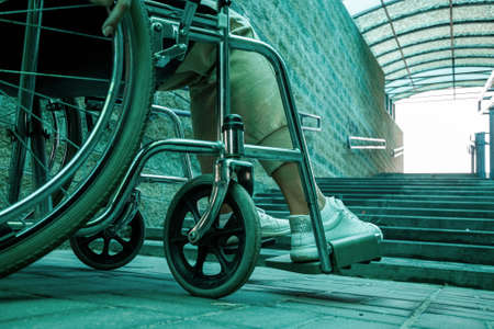 Close-up of a leg on a wheelchair in the street. Disease recognition, disability, serious condition 免版税图像