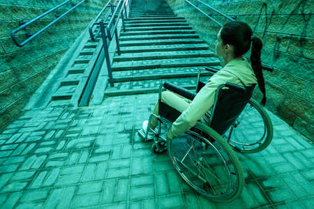 A disabled girl sitting in a wheelchair on the background of the stairs. The gray days of the disabled, problems of movement, illness