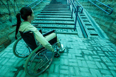 A disabled girl sitting in a wheelchair on the background of the stairs. The concept of gray everyday life of the disabled, movement problems, illness