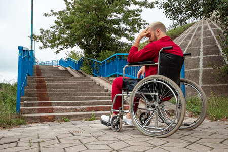 A man sits in a wheelchair, faced with difficulties alone, depression. The concept of a wheelchair, disabled person, full life, paralyzed, disabled person, health care 免版税图像