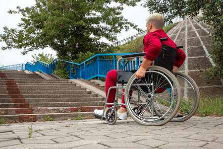 A disabled man sits in a wheelchair in front of the stairs. The concept of a wheelchair, disabled person, full life, paralyzed, disabled person, health care, loneliness 免版税图像
