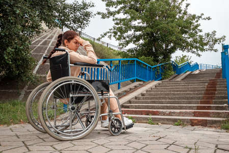 The girl is sitting in a wheelchair facing difficulties alone, depressed. The concept of a wheelchair, disabled person, full life, paralyzed, disabled person, health care
