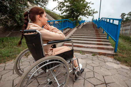 A young disabled girl sits in a wheelchair in front of the stairs. The concept of a wheelchair, disabled person, full life, paralyzed, disabled person, health care, loneliness