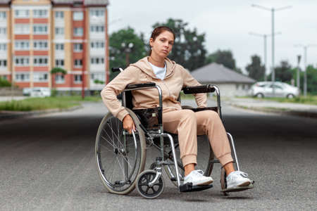 A young disabled girl sits in a wheelchair on the street. The concept of a wheelchair, disabled person, full life, paralyzed, disabled person, health care