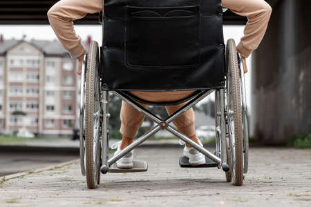 Close-up of legs in a wheelchair. The girl is disabled. The concept of a wheelchair, disabled person, full life, paralyzed, disabled person, health care
