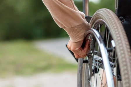 Close-up of a hand on a wheelchair wheel. The concept of a wheelchair, disabled person, full life, paralyzed, disabled person, happy life
