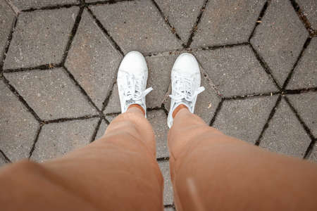 Legs in white sneakers and beige pants top view. Selfie is great for any use