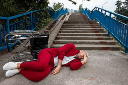 On the ground near the stairs lies a disabled man near the wheelchair. The concept of a wheelchair, disabled person, full life, paralyzed, disabled person 免版税图像