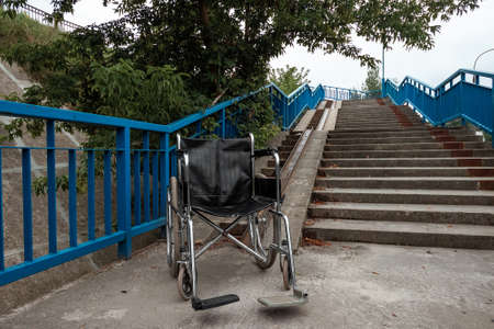 The concept of a wheelchair on the stairs turned over, disabled, full life, paralyzed. Problems for the disabled person