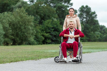 A man on a wheelchair with a girl spend time in the park. The man is disabled. The concept of a wheelchair, disabled person, full life, paralyzed, disabled person, health care