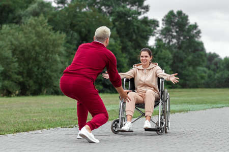 A girl on a wheelchair with a man spend time in the park. The young woman is disabled. The concept of a wheelchair, disabled person, full life, paralyzed, disabled person, health care 免版税图像