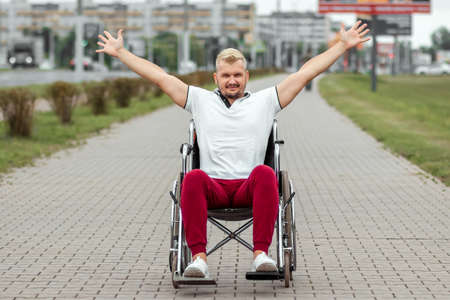 A disabled man sits in a wheelchair on the street. The concept of a wheelchair, disabled person, full life, paralyzed, disabled person, health care