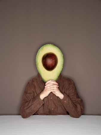 merged: Man with avocado (sliced in half) in place of his head, sitting at the table Stock Photo