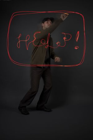 lowkey: Young man writing the word HELP with light in the air, model is underexposed low-key to allow for the letters to stand out Stock Photo