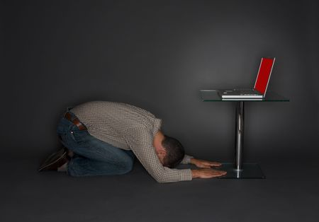 Man kneeling, bowing to a laptop computer on a pedestal