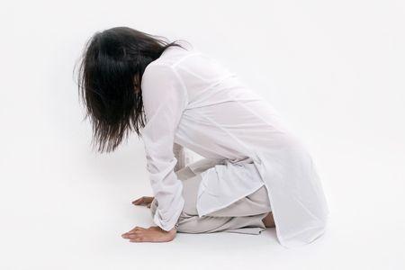 inginocchiarsi: Giovane donna vestita di bianco, in ginocchio, il volto coperto di peli, girati in studio.  Archivio Fotografico