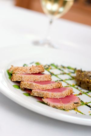 seared: Sesame seared tuna on a plate with green (wasabi) sauce, glass of white wine in the background Stock Photo
