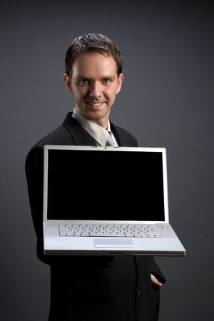 Young businessman holding a laptop (dark gray background version) photo