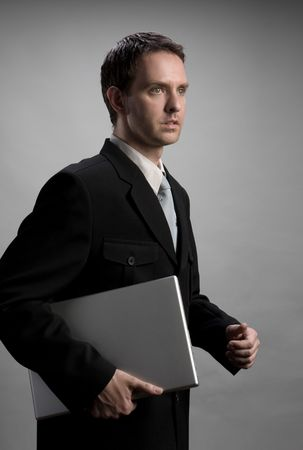 Young businessman walking, holding a laptop photo