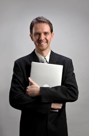 Young businessman holding a laptop (light gray background version) photo