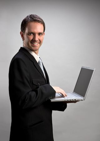 Young businessman holding a laptop, typing photo