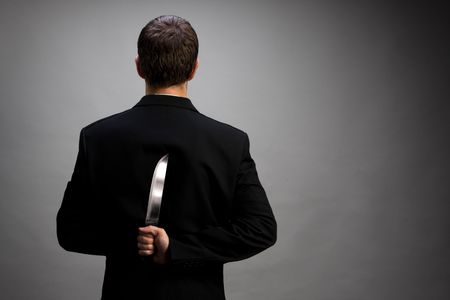 stabbing: A man in suit holding knife behind back (light gray background version) Stock Photo