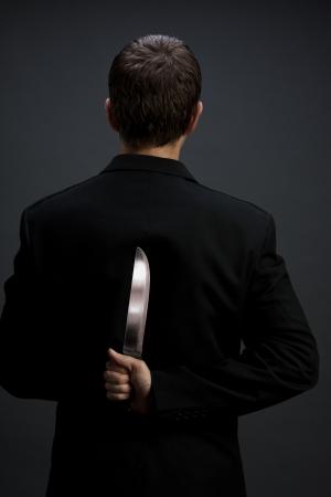 sicario: Un hombre en traje celebraci�n cuchillo detr�s de la espalda (gris oscuro fondo versi�n, vertical close-up)  Foto de archivo