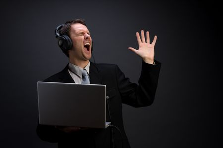 A man in suit singing, headphones plugged into a laptop