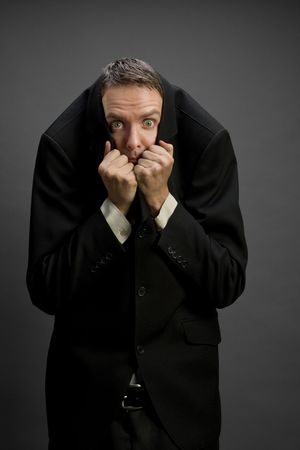 occhi sbarrati: Giovani in cerca d'affari paura, che copre la testa con la tuta giacca, gli occhi ben aperti
