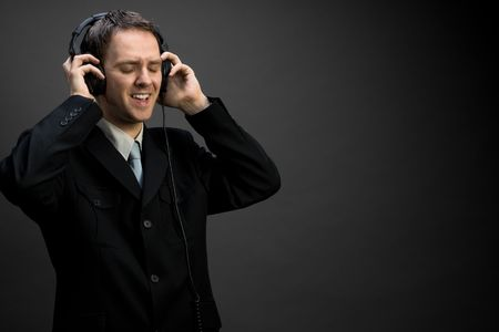 A man in suit singing, wearing headphones, eyes closed Stock Photo - 3126107