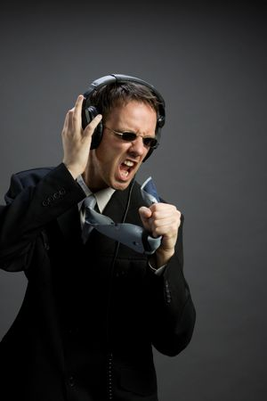 A man in suit singing, wearing headphones and sunglasses, using his tie as a microphone Stock Photo - 3126108