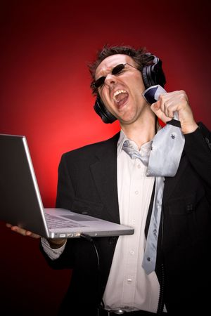 A man in suit singing, wearing headphones and sunglasses, holding a laptop, using his tie as a microphone Stock Photo - 3126113