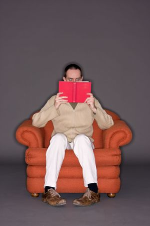 suspens: Jeune homme lisant un livre, surpris d'expression, les yeux grands ouverts Banque d'images