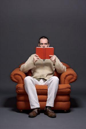 occhi sbarrati: Giovane uomo leggendo un libro, espressione sorpresa, gli occhi ben aperti